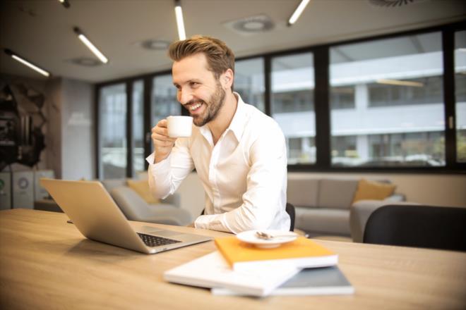 Uomo davanti al computer mentre sorseggia il caffè