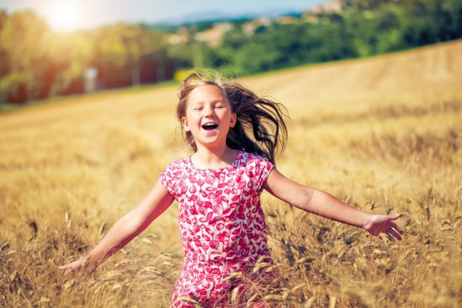 Bambina corre felice in un campo di grano