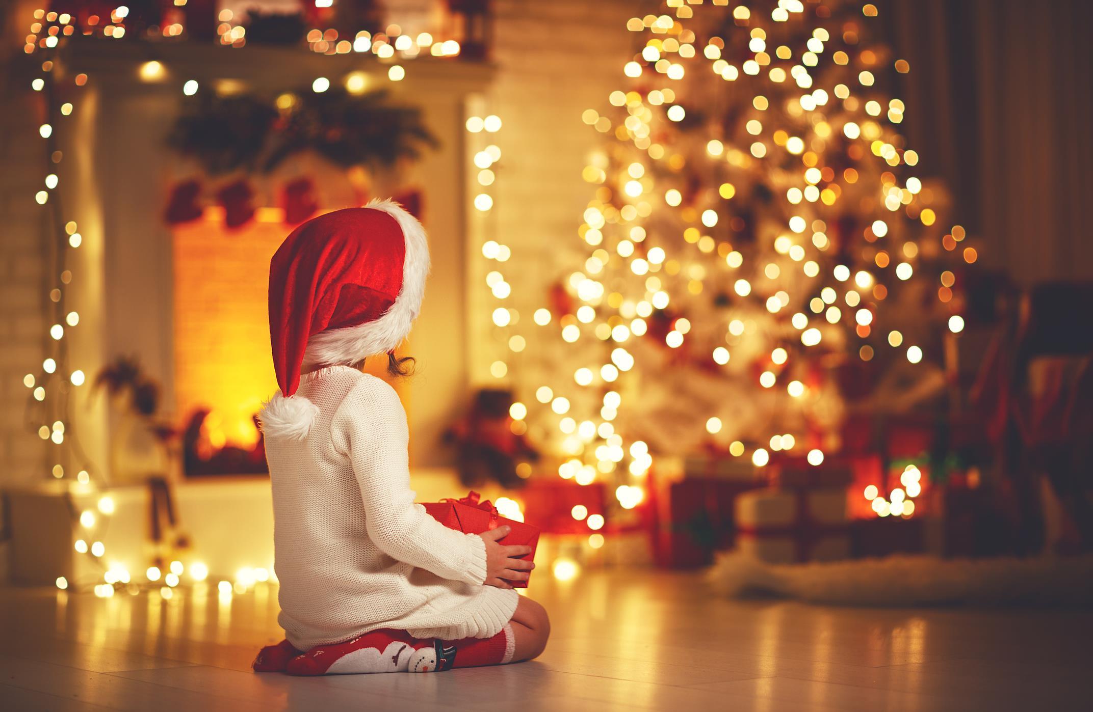 Bambina seduta con un regalo tra le mani che guarda l'albero di natale