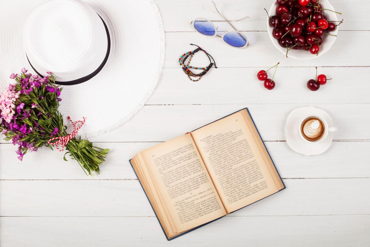 Libro su un tavolo con cappello e cappuccino