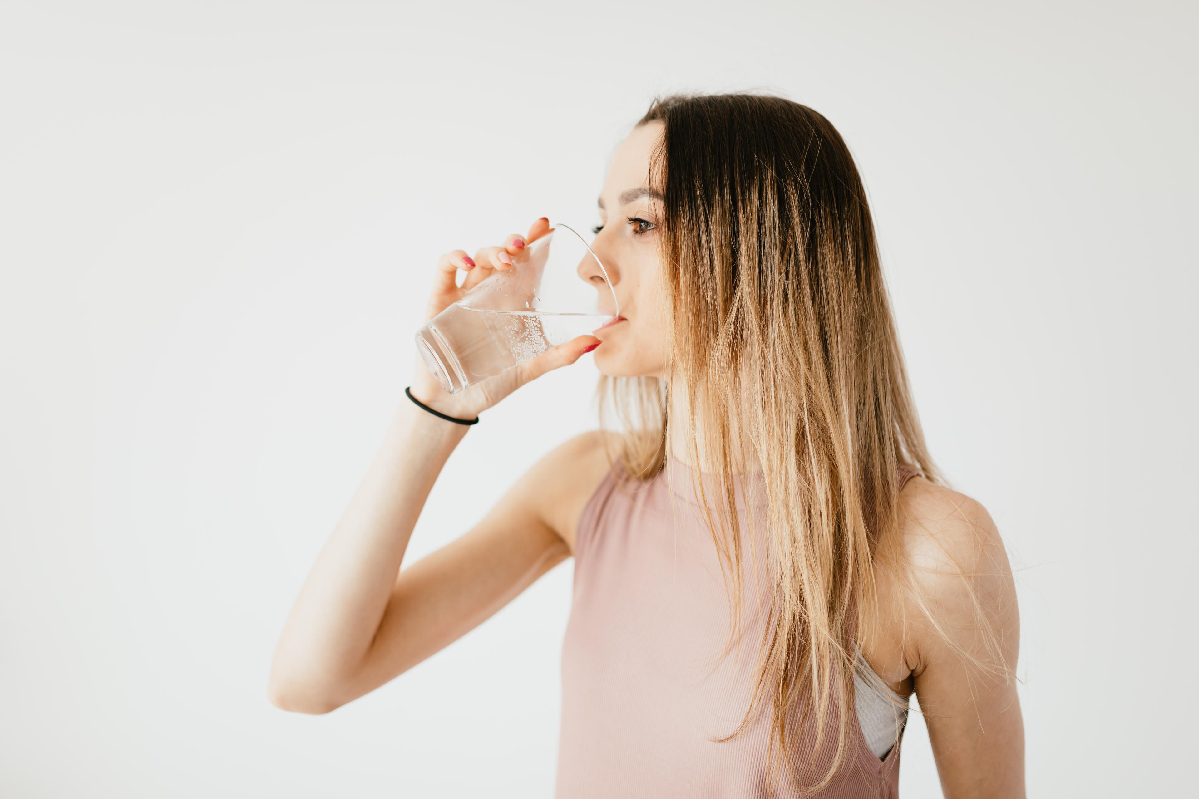 Ragazza molto magra che beve acqua