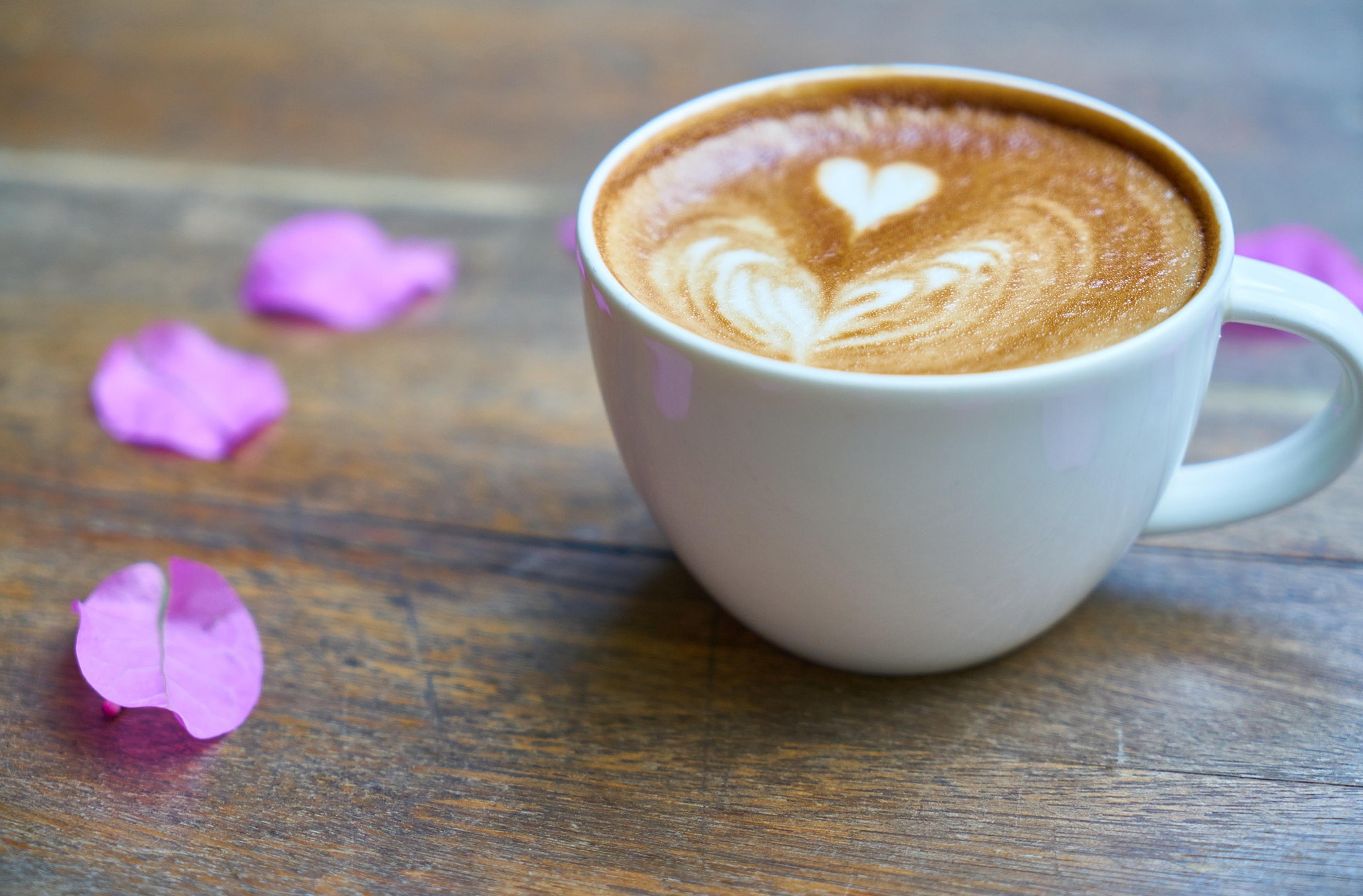 Tazzina di caffè con petali di rosa