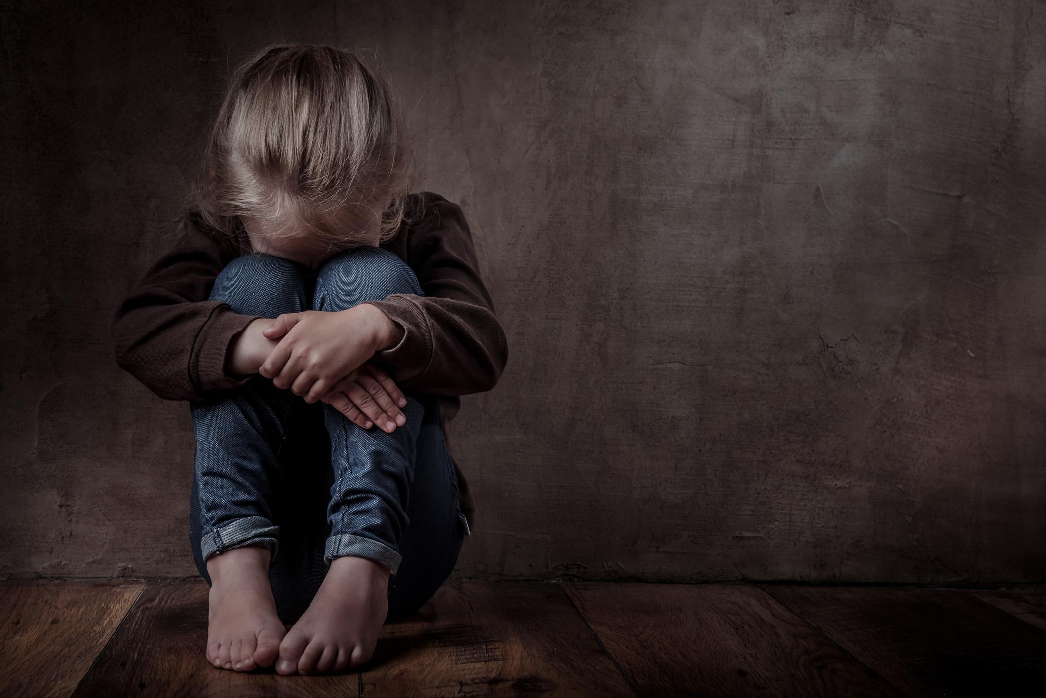 Bambina seduta a terra con le gambe al petto e la testa chinata su di esse