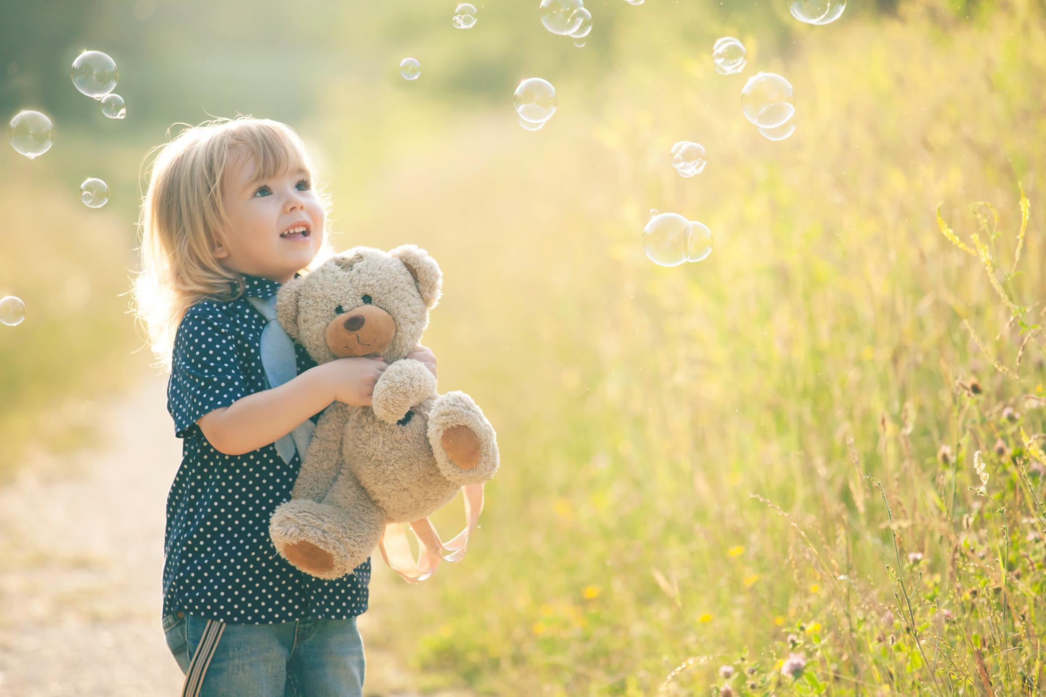 Bambina con un peluche in braccio