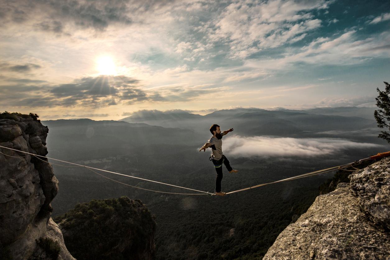 Uomo cammina su un filo sospeso tra due monti