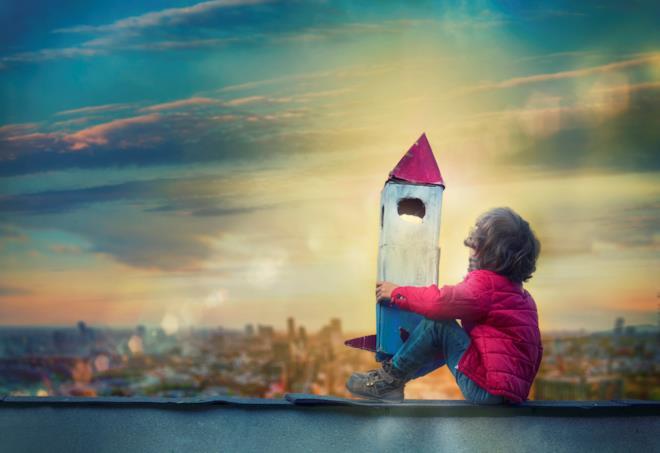 Bambino guarda il cielo con un razzo di cartone