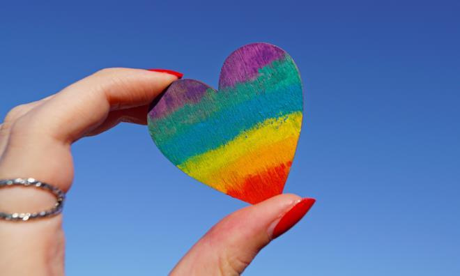Persona tiene cuore multicolore in mano