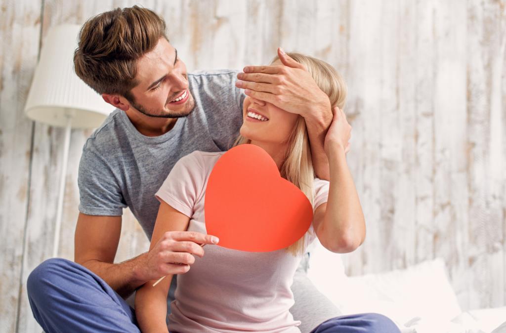 Un ragazzo abbraccia una ragazza facendole la sorpresa di un cuore di cartone