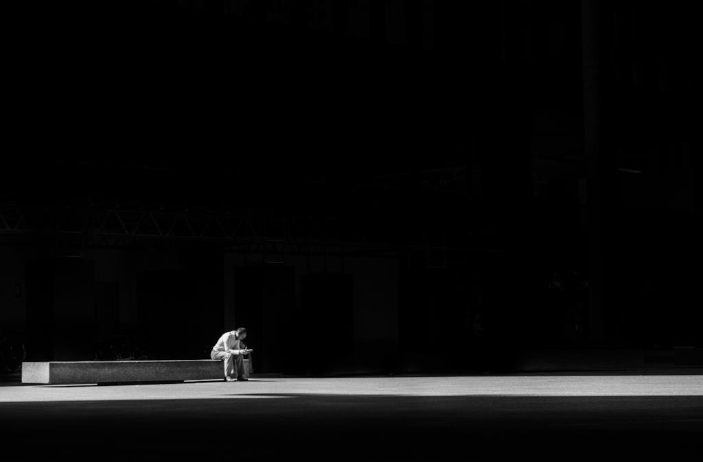 Uomo seduto su una panchina solo