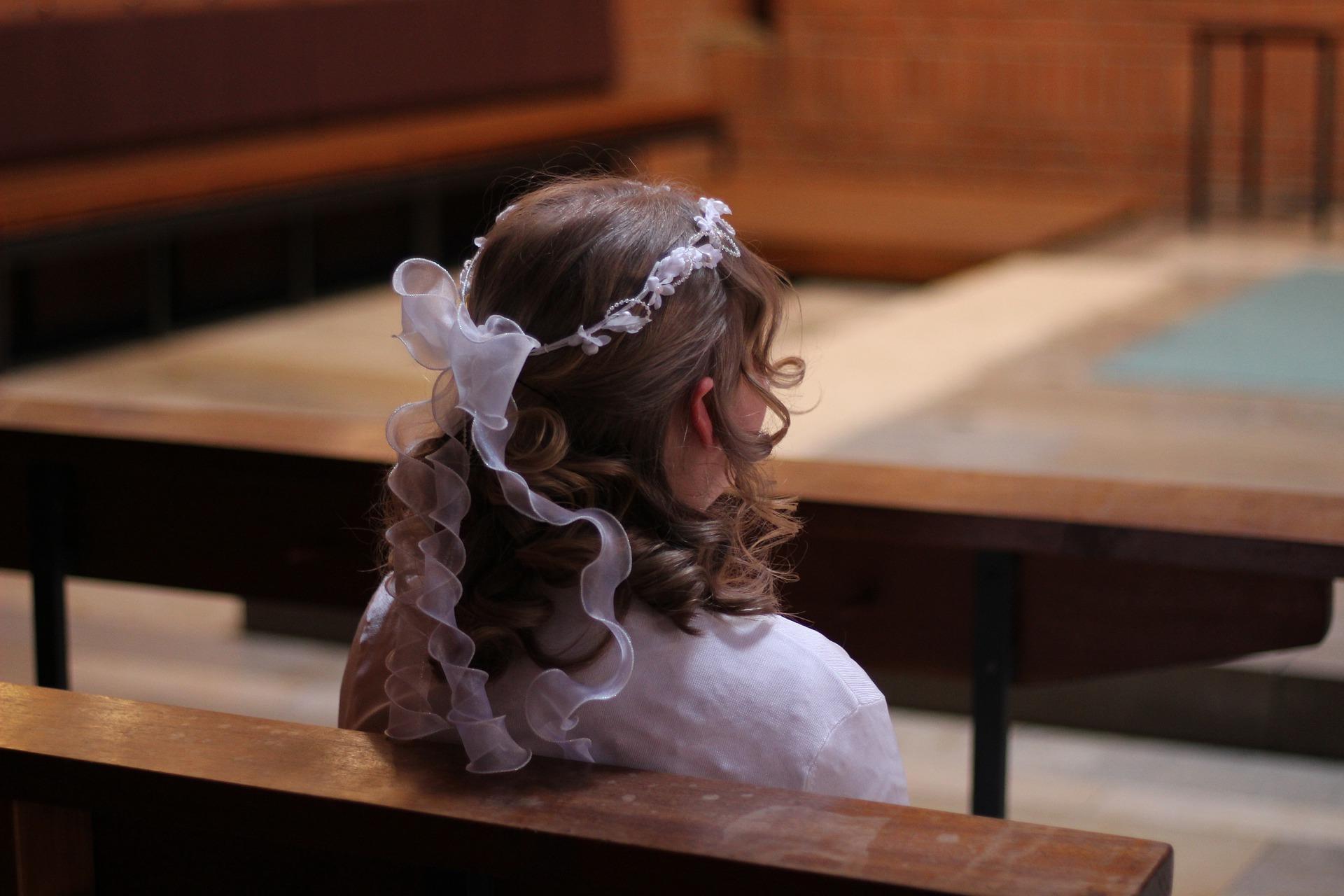 Bambina seduta in chiesa per la Santa Cresima