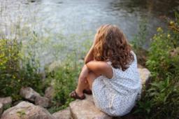 Ragazza seduta sul bordo di un lago con le mani sul volto