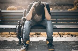 Ragazzo seduto su una panchina con le mani tra i capelli